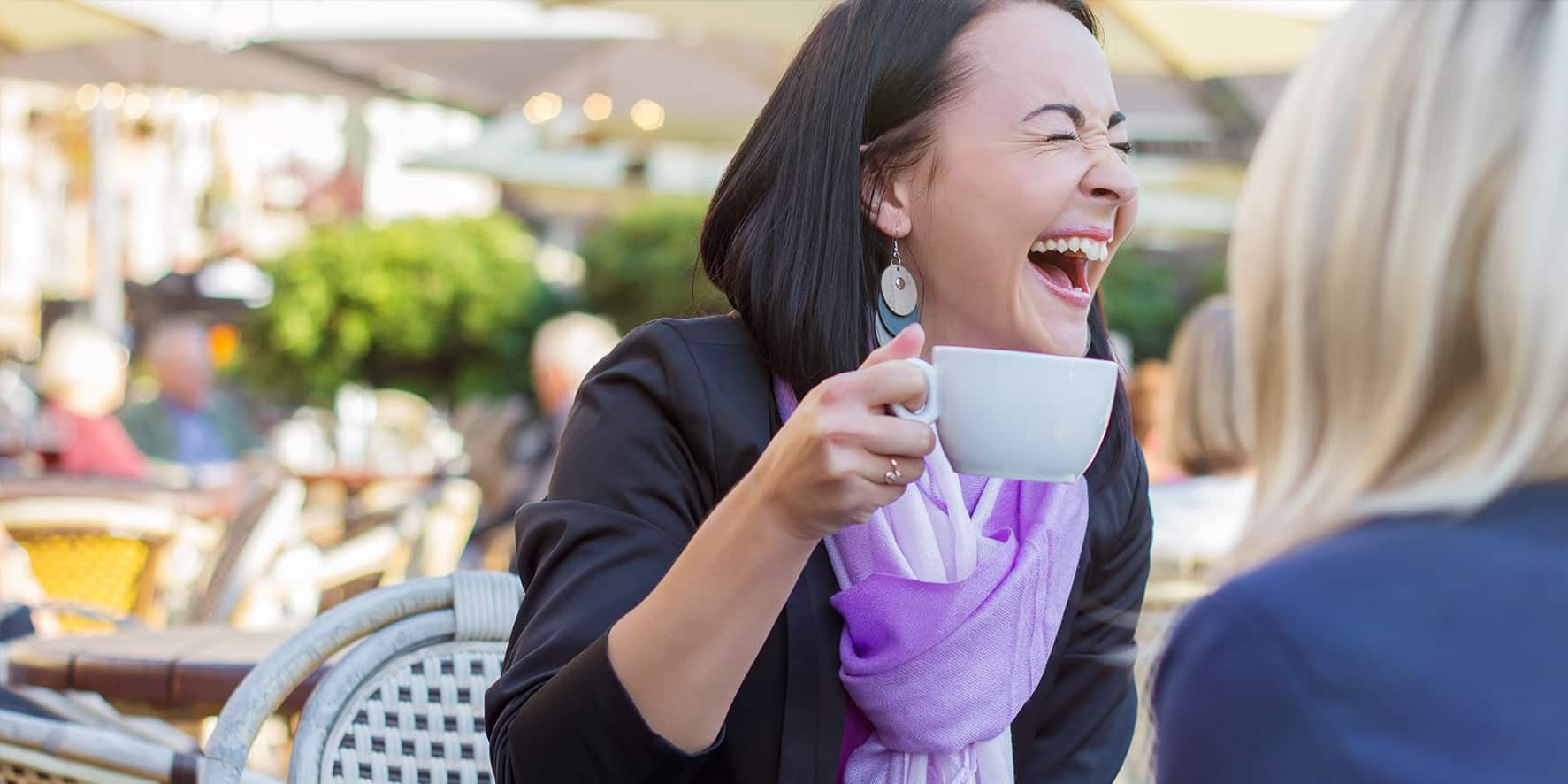 A woman laughs over coffee