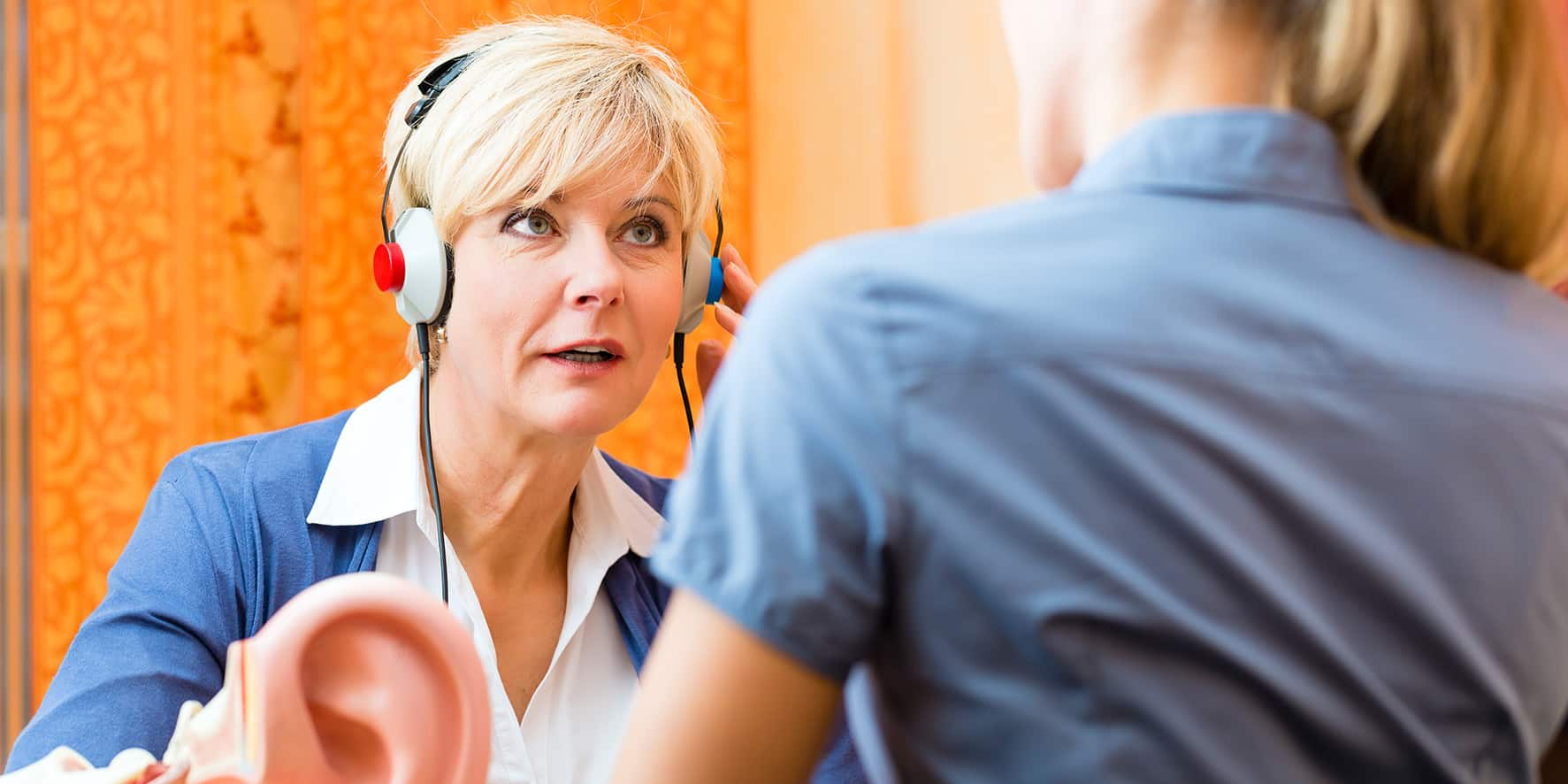 A woman listens through headphones as part of a hearing test